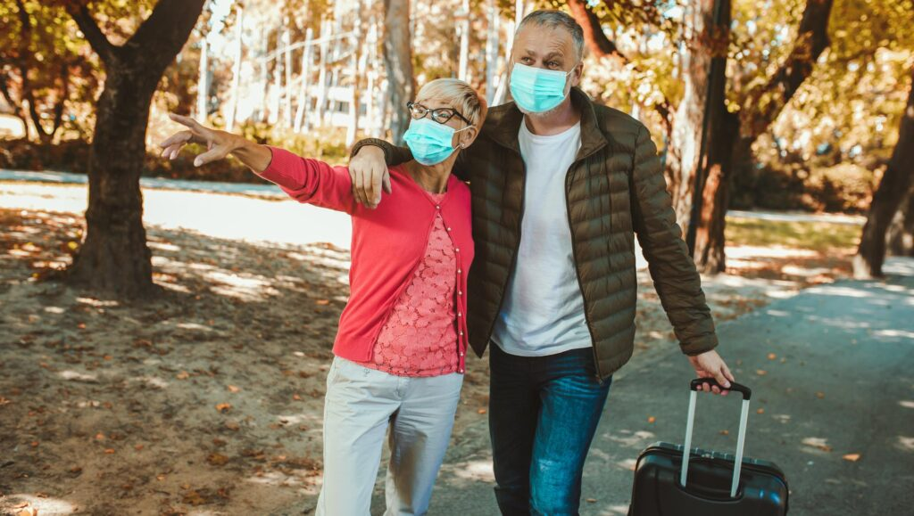 Older couple wearing face masks, traveling in fall